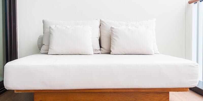 lit double d'hotel avec alese jetable et oreillers