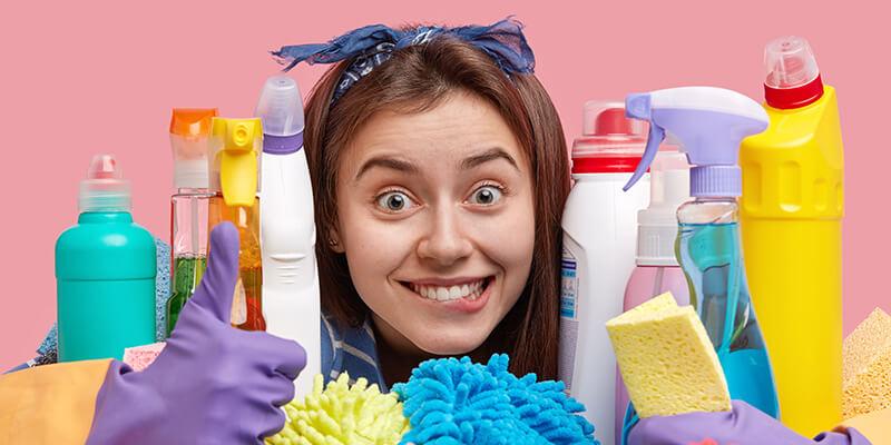 femme contente de faire le menage avec tous les produits